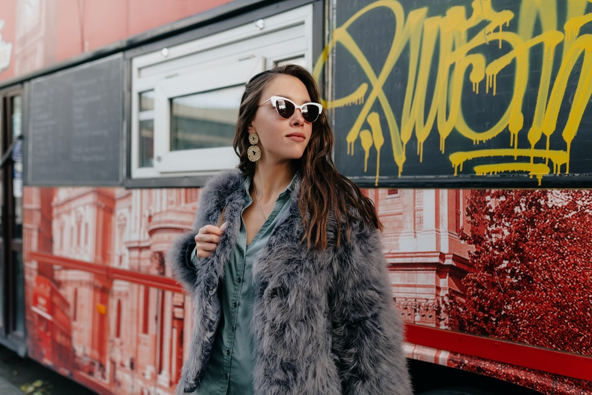 A stylish woman wears sunglasses, a gray button-down, and a gray faux fur coat.