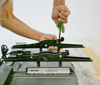 A technician is installing a wall mount on a television getting it ready to be put on a wall