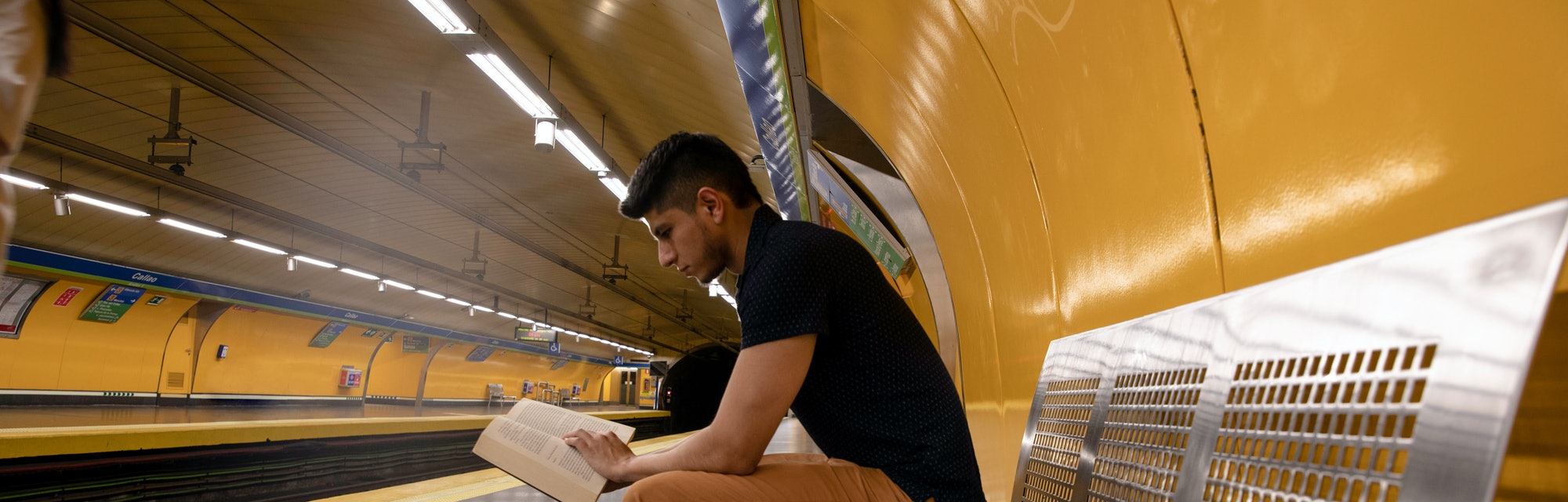 young man reading a book while waiting for the subway at the station