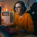 Excited Gamer Girl in Headset with a Mic Playing Online Video Game on Her Personal Computer. She Talks to Other Players. Room and PC have Colorful Warm Neon Led Lights. Cozy Evening at Home.
