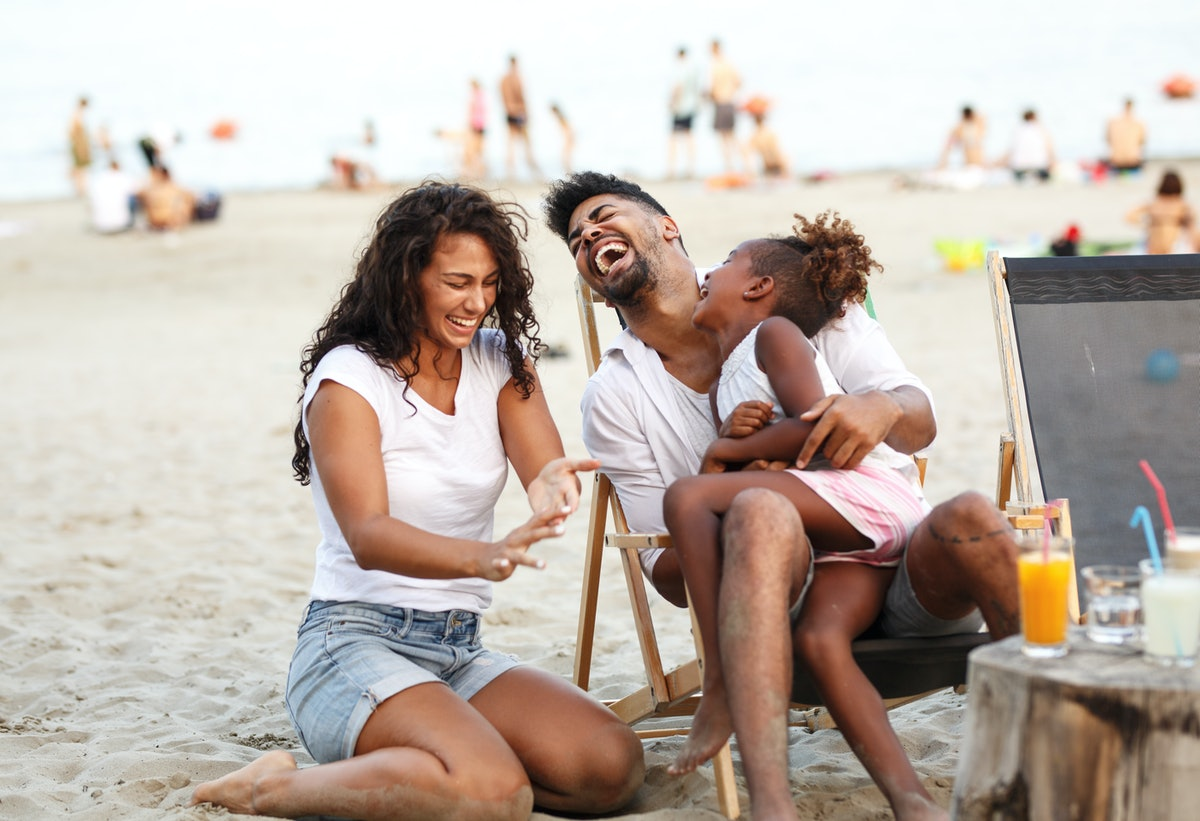 A mom, dad, and daughter laugh while spending time at the beach.