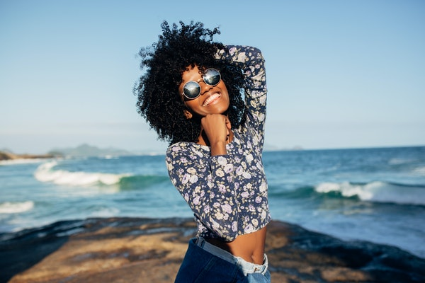 Young beautiful Brazilian girl staying on beach in Rio de Janeiro on warm sunny with embankment and tall residential houses in blurred background and laughing