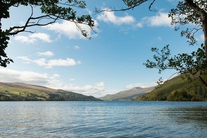 Edge of lake Loch Tay in Kenmore, which is a small village in Perthshire, in the Highlands of Scotland, located where Loch Tay drains into the River Tay.  Scenic autumnal view of lake.