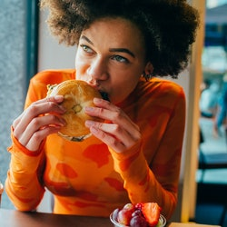 A woman eats a hamburger on a bagel. Wondering why meat makes you feel sick? Some people have stomach pain and diarrhea after eating red meat. Health experts explain.
