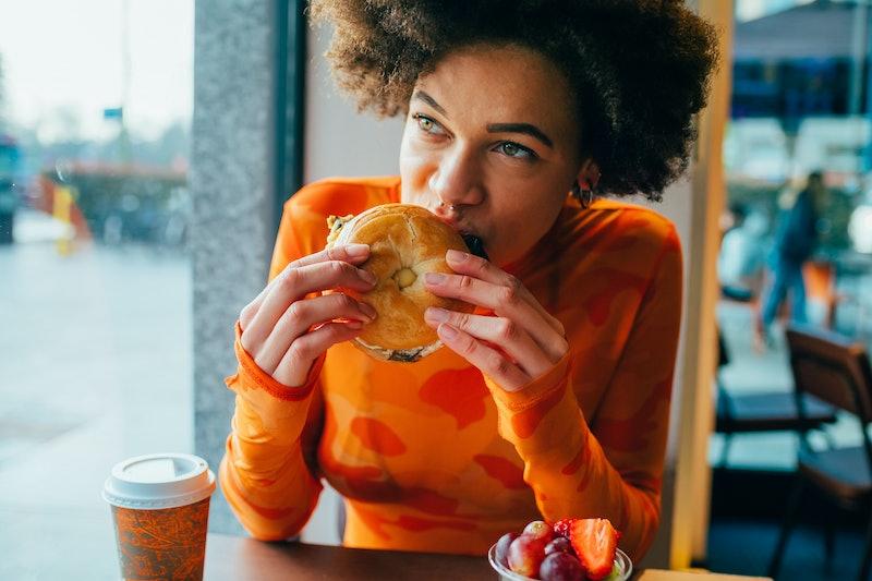 Young beautiful afro woman indoors restaurant biting hamburger - hungry diverse woman sitting restaurant eating bagel