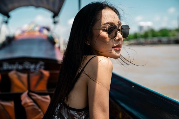 attractive female traveler wearing sunglasses look away while traveling on traditional long tail boat in Chao Phraya river.