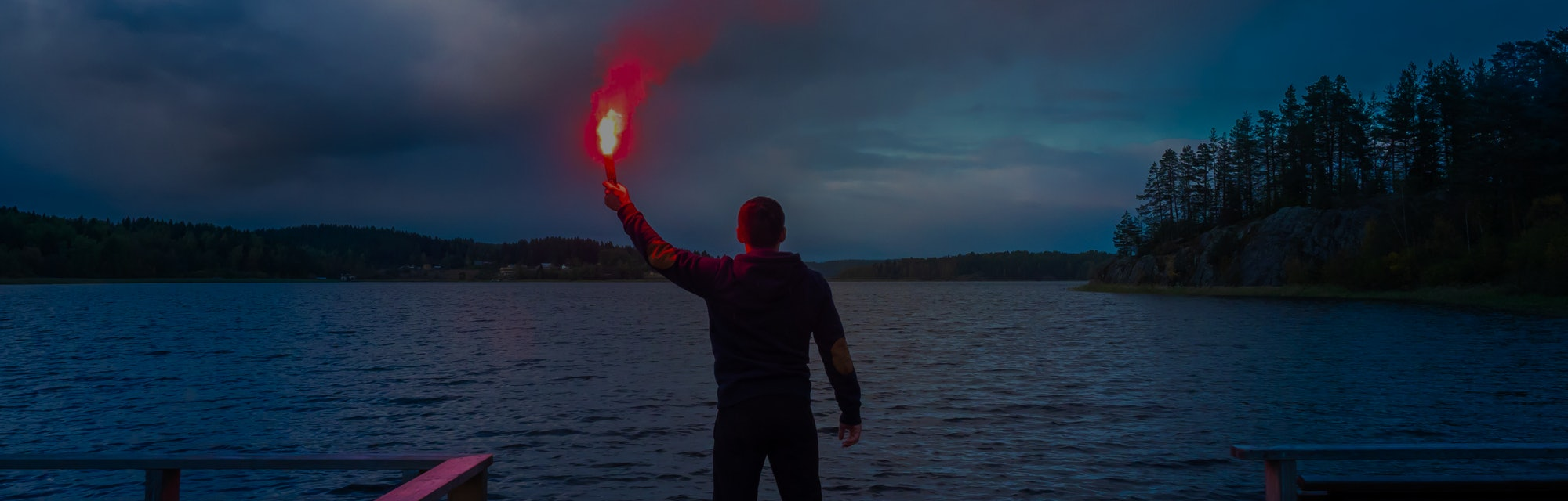 Signal for help. A man signals a torch in his hand. SOS. A man holds a torch in his hand.