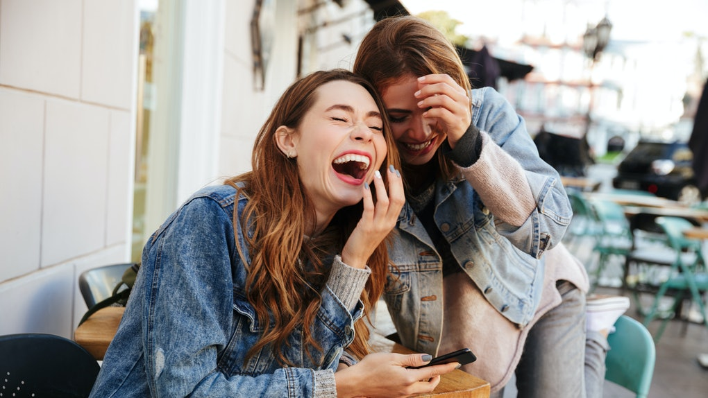 Two women wearing denim jackets laugh while looking at a mobile phone at an outdoor café.