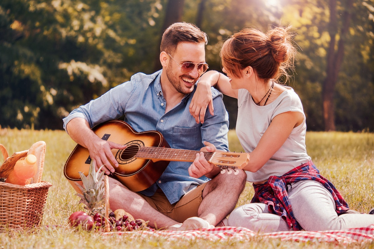 A man plays guitar for his girlfriends on a picnic outside.