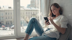Close up pretty young woman sitting on a windowsill at home and texting on her phone communication female looking message cellphone cheerful smile use internet modern smartphone slow motion