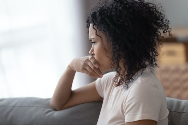 Upset African American woman thinking about bad relationships problems, break up with boyfriend close up, worried girl sitting on sofa alone at home, suffering from loneliness, feeling sad