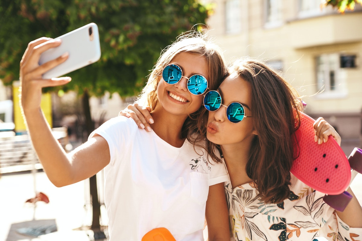Two young female stylish hippie brunette and blond women models in summer hipster clothes taking sel...