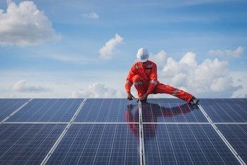 A construction worker building solar panels against a blue sky.