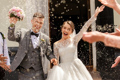 Happy wedding photography of bride and groom at wedding ceremony. Wedding tradition sprinkled with r...