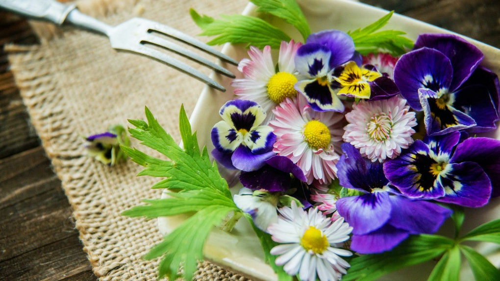 A plate filled with edible flowers sits on a table with a fork resting against it.