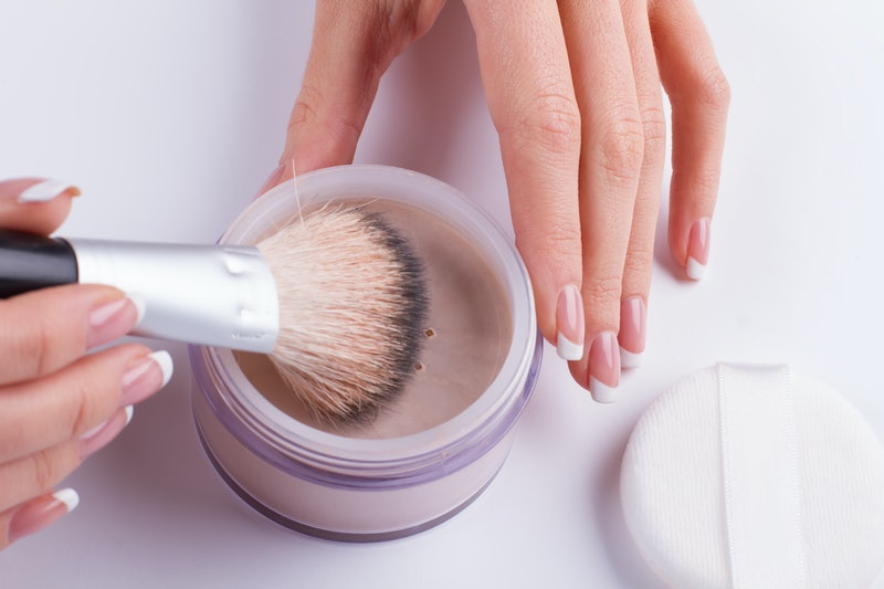 Beautiful french manicure. Women's hands holding the powder and brush.