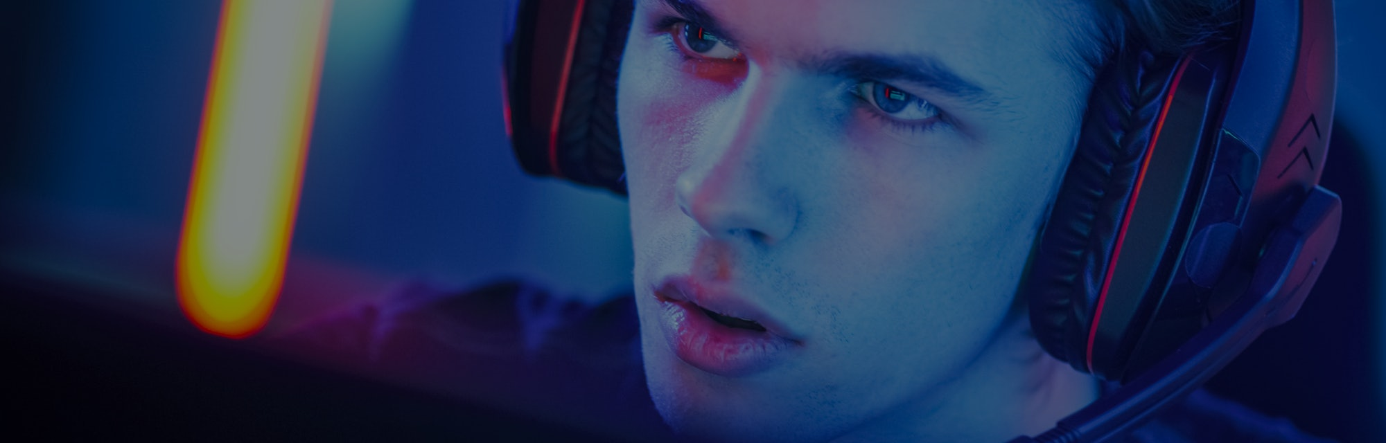 Portrait of the Young Handsome Pro Gamer Playing in Online Video Game, talks with Team Players through Microphone. Neon Colored Room. e-Sport Cyber Games Internet Championship.