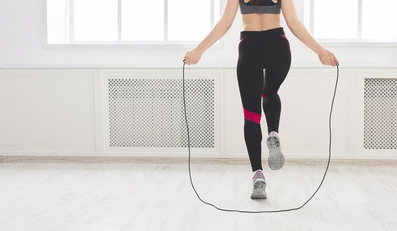 Unrecognizable woman jumping over the skipping rope in studio, crop, panorama, free space