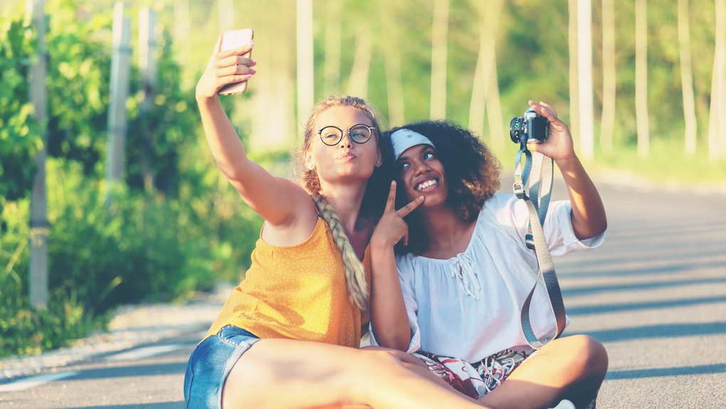 Female friendship concept with multiethnic girls couple taking selfie outdoors in countryside road - Lgbtq genuine love relationship with happy millennial girlfriends having fun