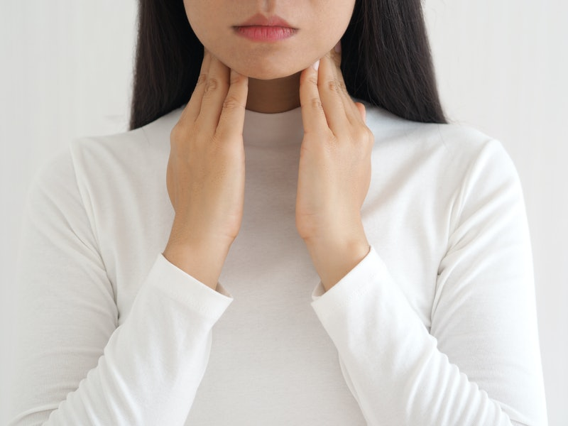 A woman holds her hands up to her throat, monitoring her sore throat for symptoms of coronavirus.