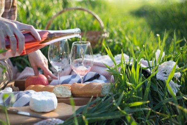 Summer - Provencal picnic in the meadow.  girl  pours wine into glasses  near a picnic basket and baguette
