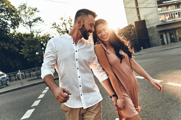 A happy couple holds hands while walking on a street at sunset in the summertime.