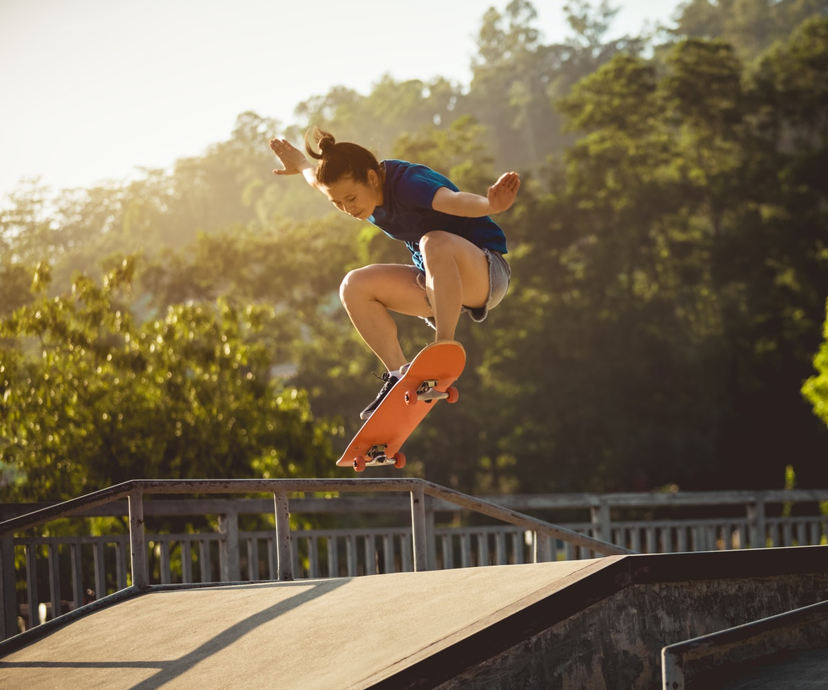 Skateboarder skateboarding at skatepark ramp. A woman hula hoops. These nostalgic outdoor activities make excellent workouts as an adult.