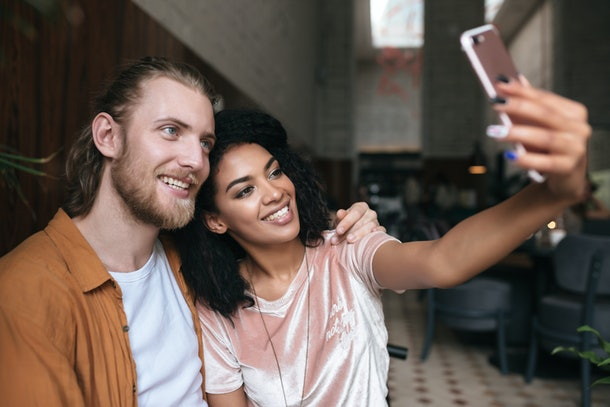 A trendy young couple poses for a selfie in a bar.