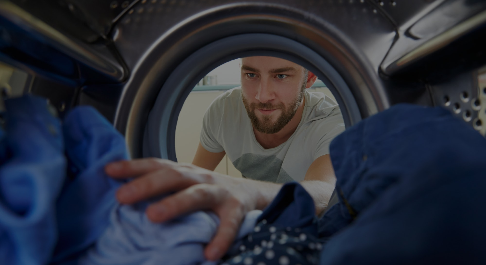 Man Doing Laundry Reaching Inside Washing Machine