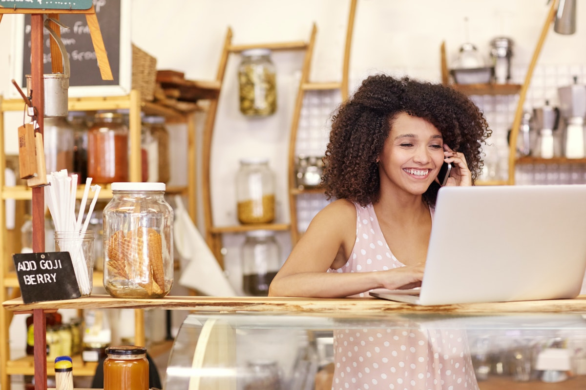 Happy young coffee shop owner talking on he mobile phone while typing on her laptop on the counter