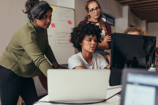 Software engineers working on project and programming in company. Startup business group working as team to find solution to problem. Woman programmer working on computer with colleagues standing by.
