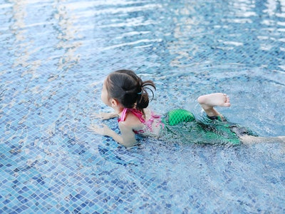 Little Asian child girl wear mermaid swimming suit has fun at the pool.