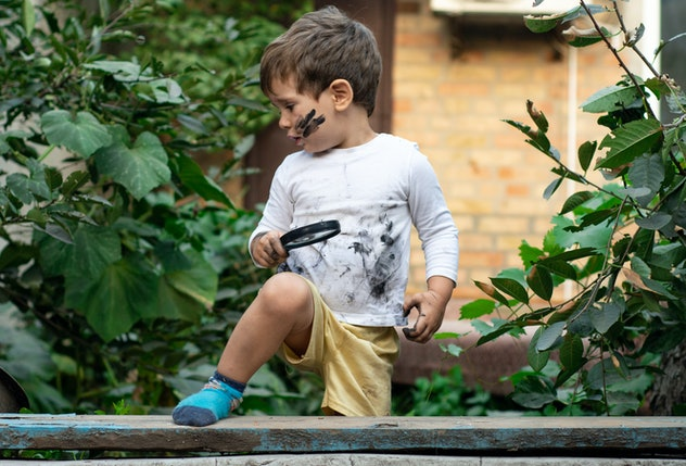 Little toddler boy with dirty face and dirty clothes looking through a magnifying glass on nature. C...