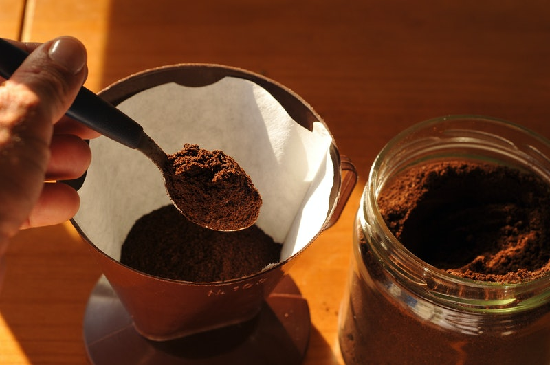 Preparing coffee, coffee strainer with coffee and spoon.