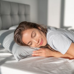 Bed Asian girl happy smiling sleeping on stomach sleeper resting head on foam pillow. Healthy sleep.
