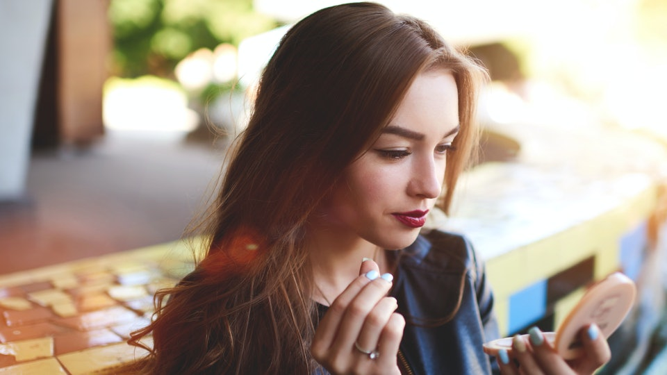 Attractive sexy woman making make-up woman applying lipstick outdoors. Charming hipster girl rouge lips with red color sitting in coffee shop, woman applying lipstick