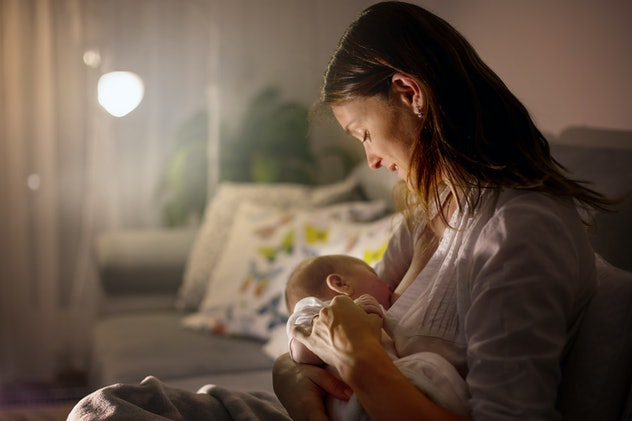 Young beautiful mother, breastfeeding her newborn baby boy at night, dim light. Mom breastfeeding in...