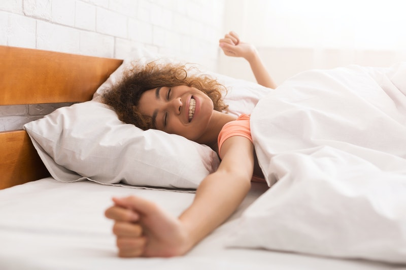 Happy woman waking up after sleep, lying in bed in the morning
