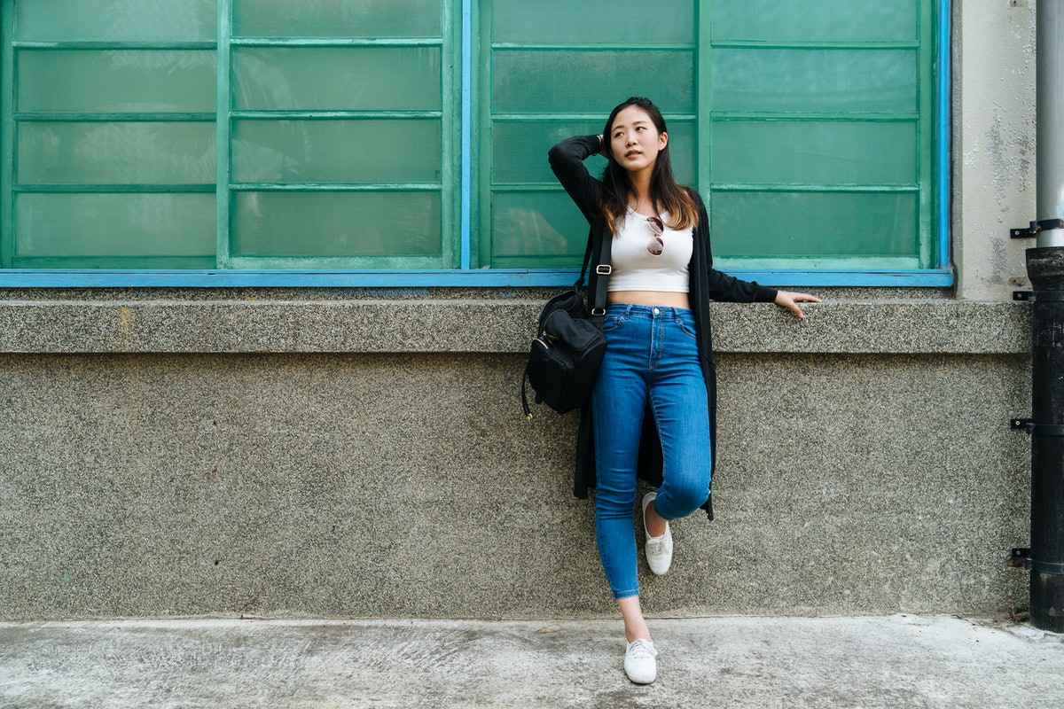 A woman leans against a wall, while wearing a white crop top and jeans.