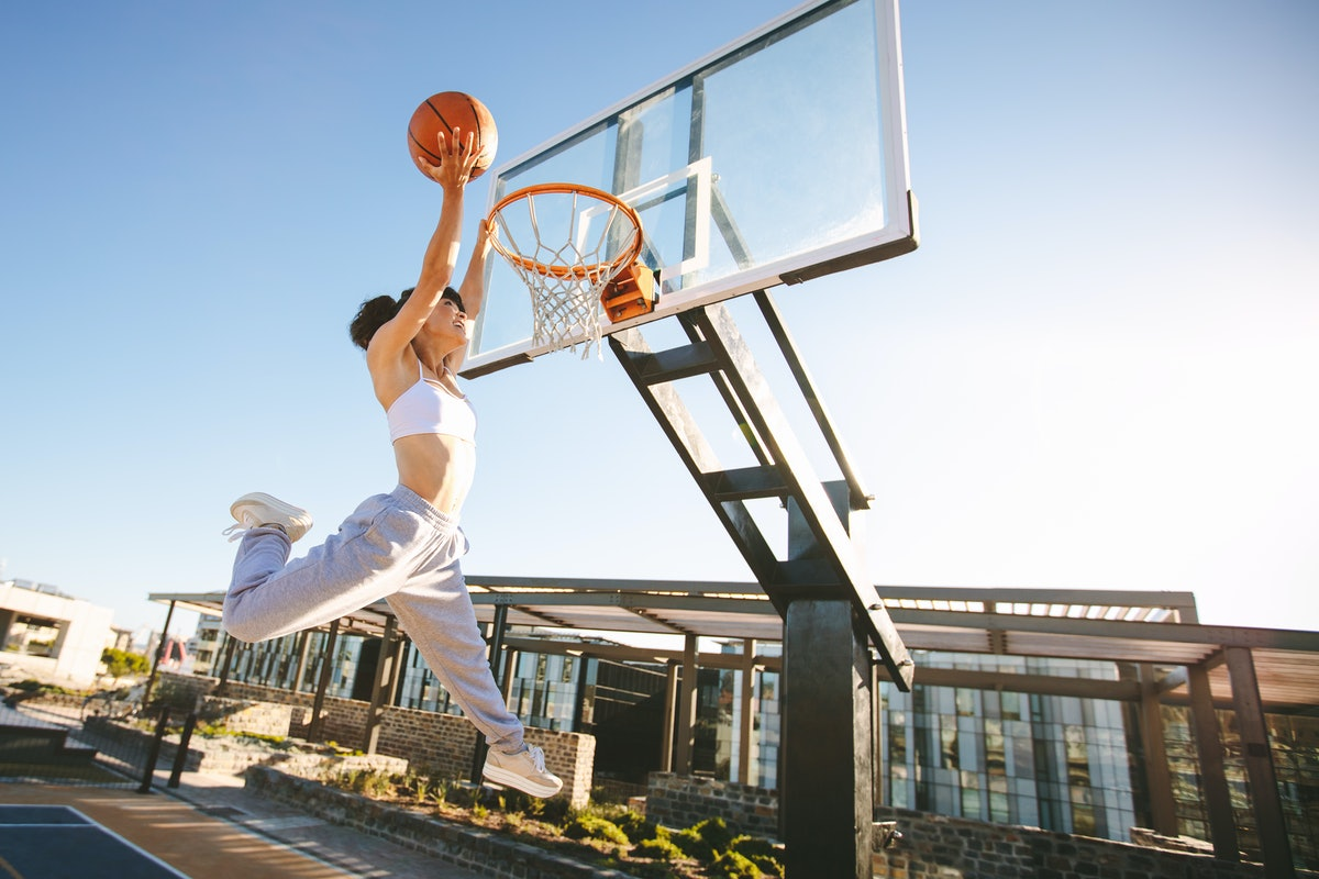 Woman basketball player slam dunking on street court. Female playing basketball outdoors on summer day.