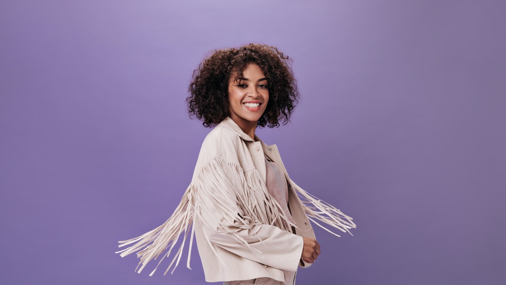 Attractive woman in jacket with fringe whirls on isolated background. Portrait of young brunette girl in beige outfit dancing on purple backdrop