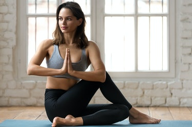 Young attractive woman practicing yoga, doing Half lord of the fishes exercise, Ardha Matsyendrasana...