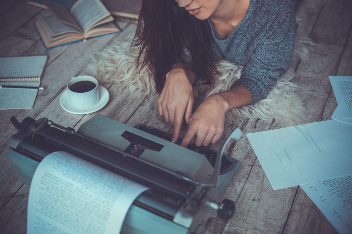 Young woman writer in library at home creative occupation working on typewriter