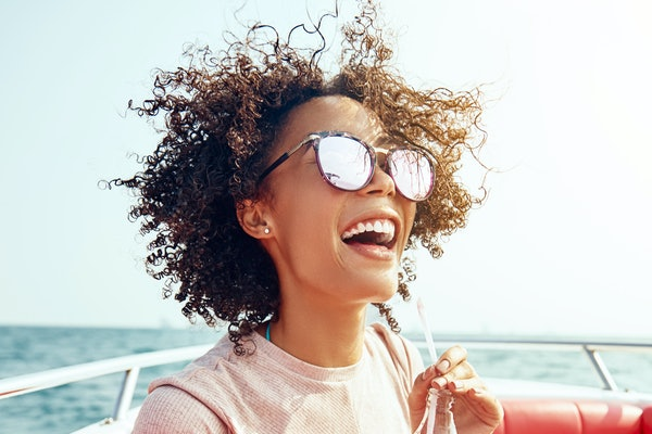 Laughing young woman wearing sunglasses and enjoying a drink while standing on a boat during summer vacation