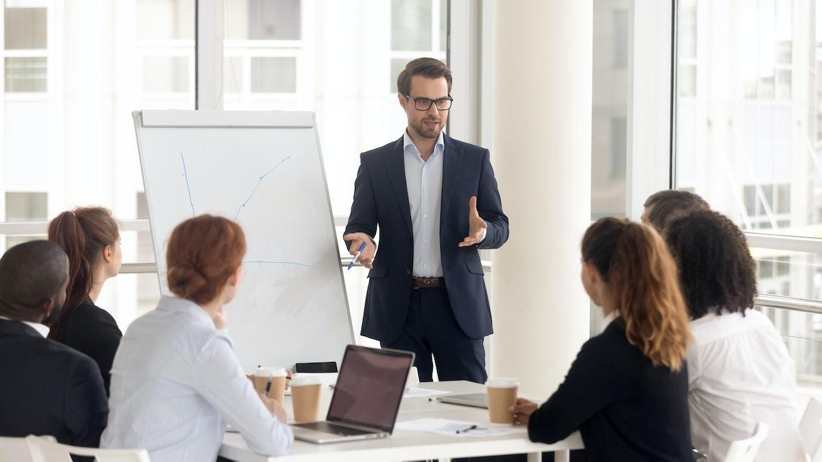 Male business coach speaker in suit give flipchart presentation, speaker presenter consulting traini...