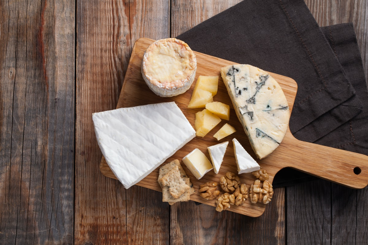 Tasting cheese dish on a wooden plate. Food for wine and romantic, cheese delicatessen on a wooden r...