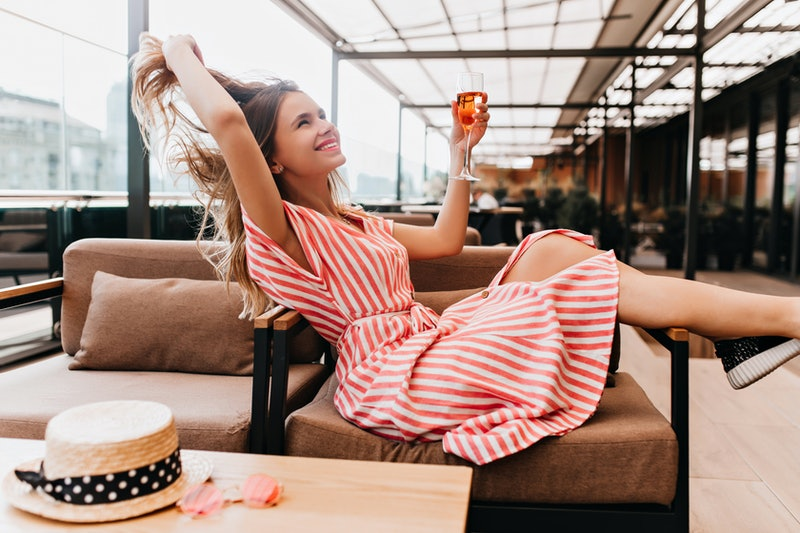Ecstatic blonde girl playing with her hair while chilling in cafe. Inspired young woman in striped dress enjoying champagne in restaurant in summer weekend.