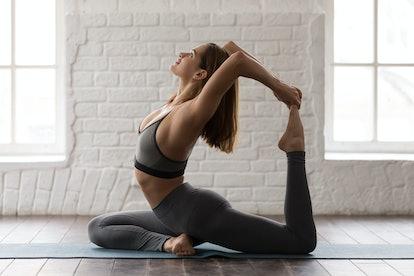 Young sporty woman in grey sportswear, leggings and bra practicing yoga, beautiful girl sitting in R...