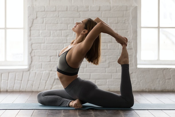 Young sporty woman in grey sportswear, leggings and bra practicing yoga, beautiful girl sitting in Rajakapotasana pose, One Legged King Pigeon exercise, working out at home or in yoga studio close up
