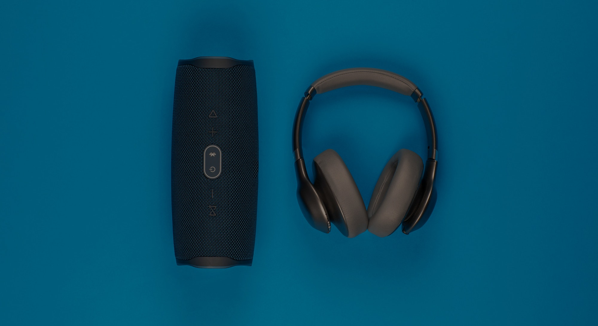 A pair of headphones next to a black speaker on blue background, shot from above.